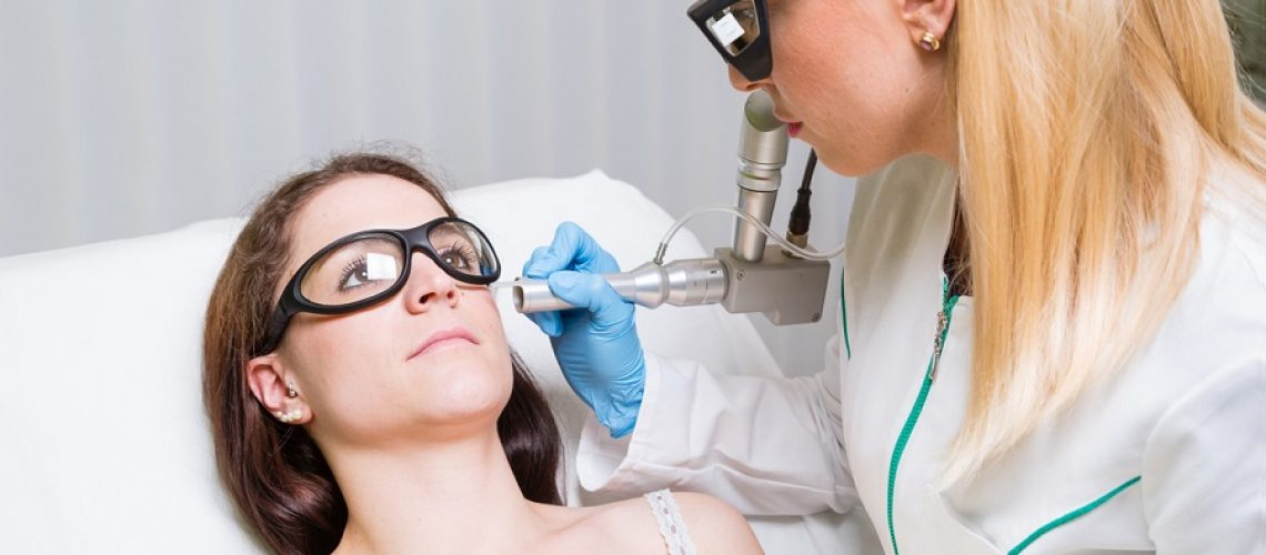 Removing liver spot from face of a young woman with medical laser.